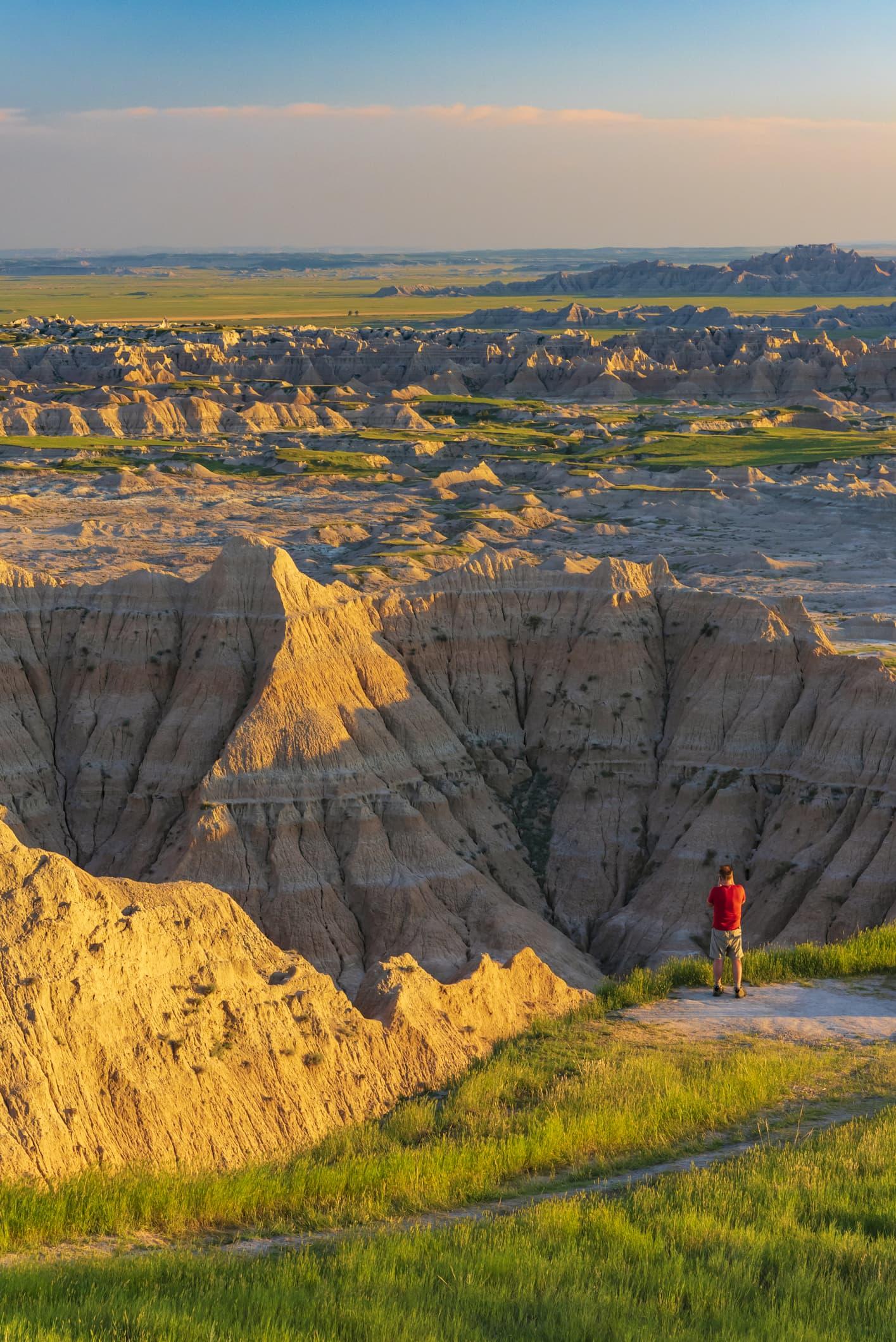 Single male photographer looks across the rocky Badlands at sunset, South Dakota, Nebraska. USA
