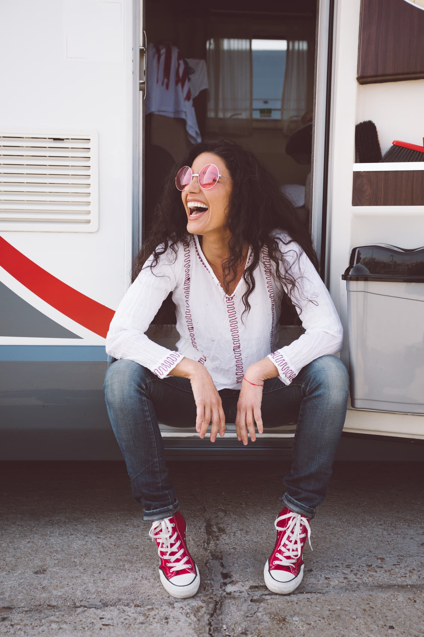 Happy woman sitting at the doorstep of campervan and looking away