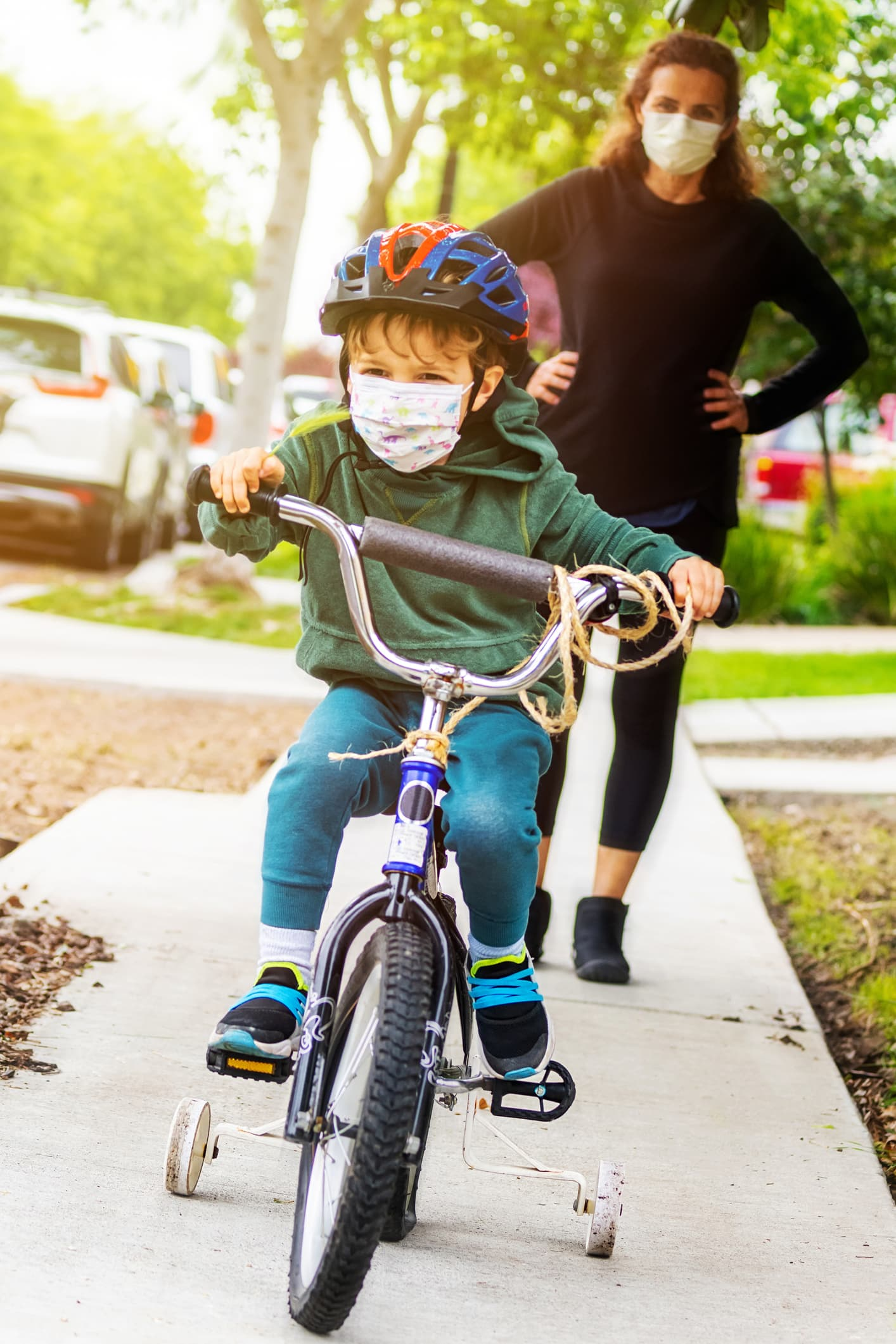 Caucasian Mature woman helping her son riding a bicycle wearing a protective mask