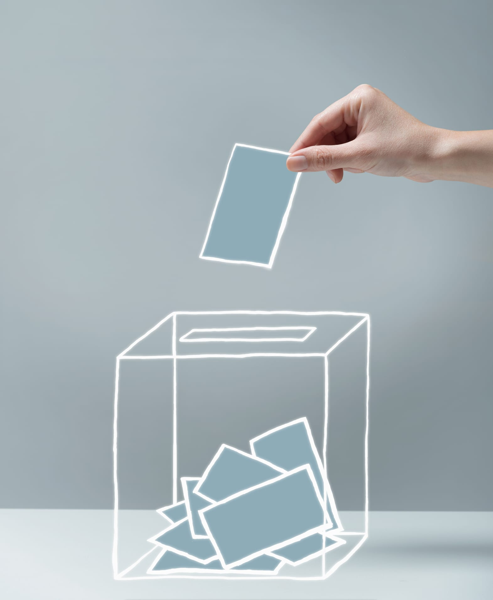 Young woman's hand about to place illustrated ballot into ballot box